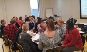 Ryhmä eri kulttuureista olevia ihmisiä istuu pöytien ääressä keskustellen.